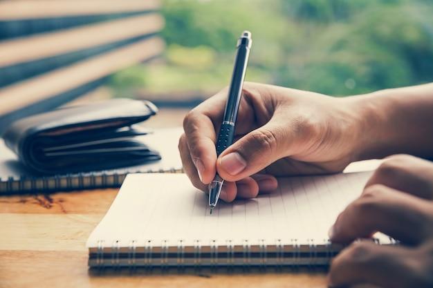 Sluit omhoog beeld van mensenhand schrijvend op notitieboekje met houten lijstachtergrond
