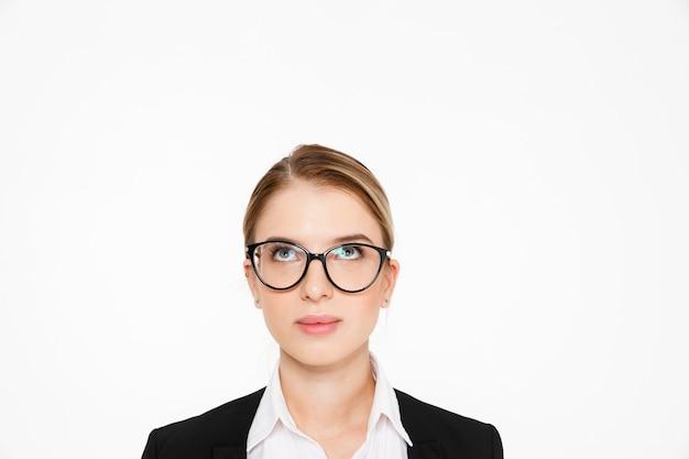 Sluit omhoog beeld van onbezorgde blonde bedrijfsvrouw die in oogglazen omhoog over wit kijken