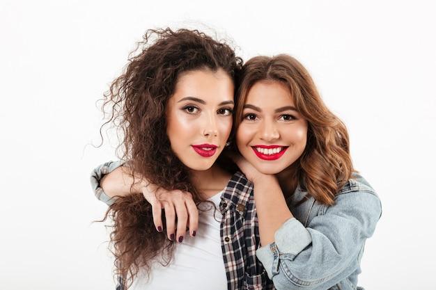 Sluit omhoog beeld van twee glimlachende meisjes die samen over witte muur stellen