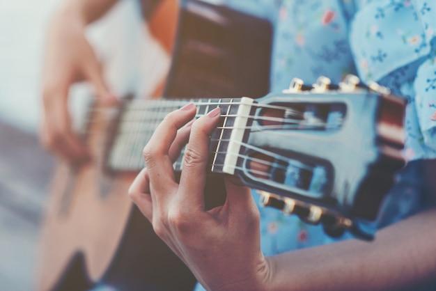 Sluit omhoog beelden van de handen die van de vrouw akoestische gitaar spelen