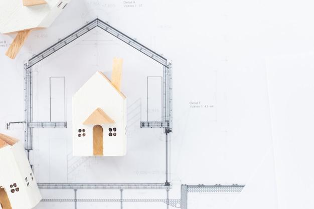 Sluit omhoog beelden van miniatuur witte huizen op architecturaal blauwdrukdocument met exemplaarruimte voor bericht