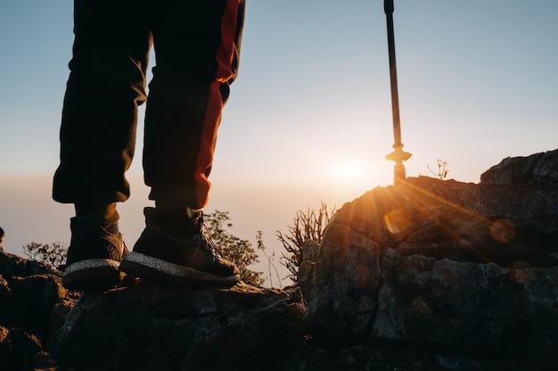 Sluit omhoog benen van de tribune van de wandelingsmens op berg met zonlicht.