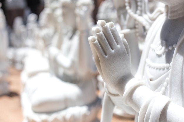 Sluit omhoog biddende hand van marmeren cijfer bij tempel