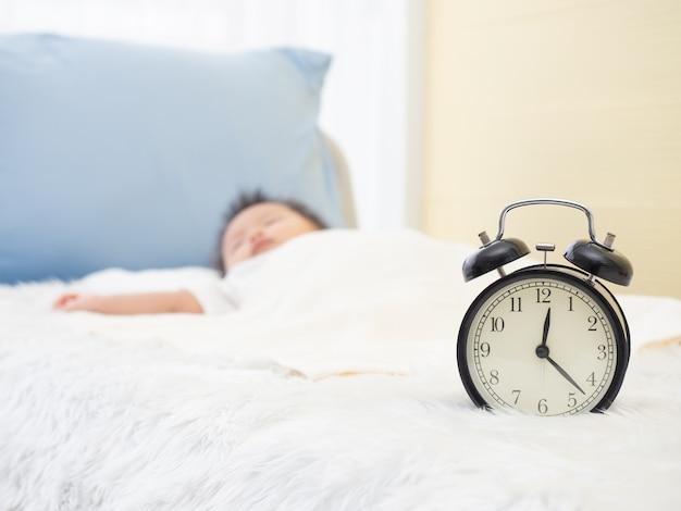 Sluit omhoog bij wekker en vaag van babyjong geitje slaapt op het bed.