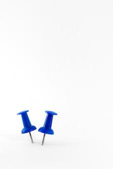 Sluit omhoog blauwe die punaise op wit wordt geïsoleerd