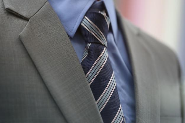 Sluit omhoog blauwe stropdas met grijs kostuum