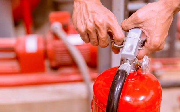 Sluit omhoog brandblusapparaat en het trekken van speld op rode tank.