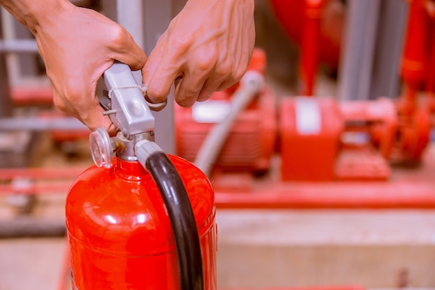 Sluit omhoog brandblusapparaat en trekkend speld op rode tank.