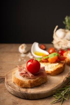 Sluit omhoog bruschettas met prosciutto en tomaten