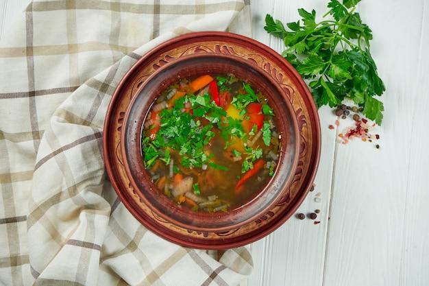 Sluit omhoog chorba-soep of hutspot met rundvlees, kruiden en hete peper in bruine kom op houten achtergrond, traditionele turkse keuken