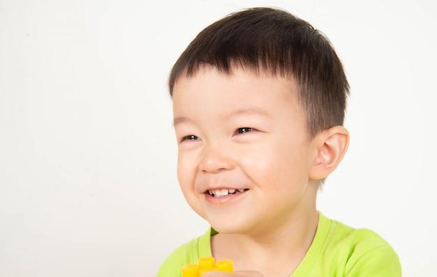 Sluit omhoog de aziatische glimlach van de peuterjongen met gelukkig gezicht