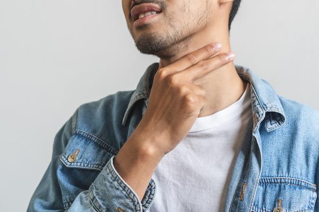 Sluit omhoog de aziatische mens wat betreft zijn hals en heb keelpijn.