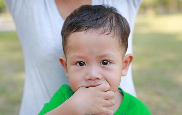 Sluit omhoog de aziatische zuigende vinger van de babyjongen in mond.
