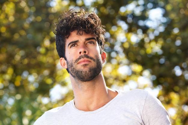 Sluit omhoog de ernstige knappe mens met baard buiten in aard