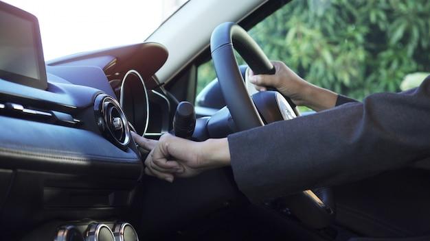 Sluit omhoog de hand van de vrouw, duwt zij starter in moderne auto.