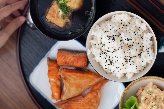 Sluit omhoog de japanse zalm van voedseltiyaki met rijstreeks die op houten lijst wordt gediend.