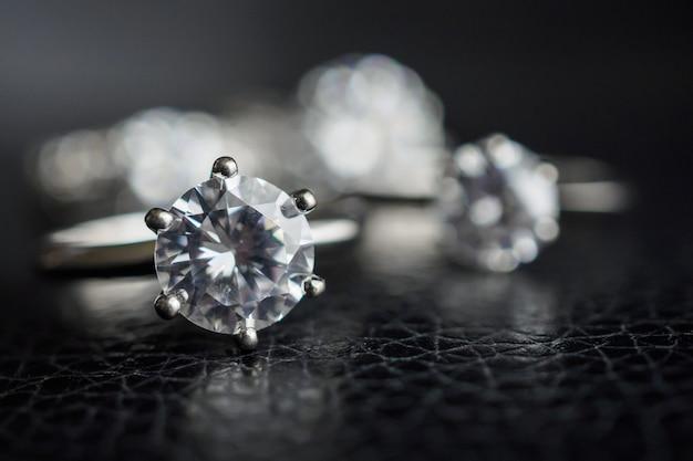 Sluit omhoog de juwelen van diamantenringen op zwart leeroppervlak