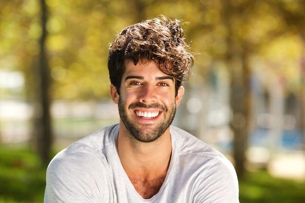 Sluit omhoog de knappe mens met baard buiten glimlachend