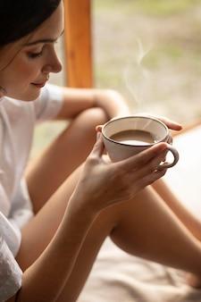 Sluit omhoog de koffiekop van de vrouwenholding