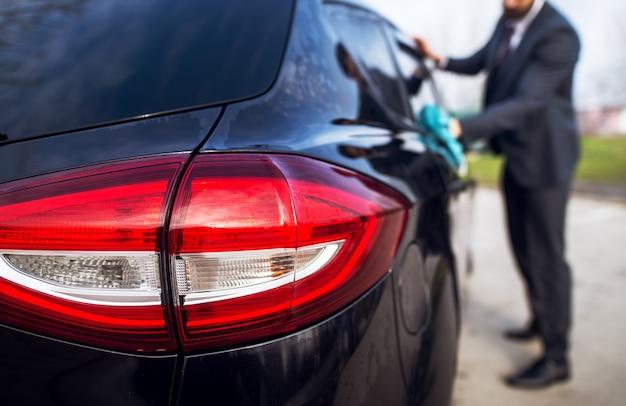 Sluit omhoog de mening van autolichten van zwarte auto en eigenaar in een kostuum terwijl het schoonmaken met een microvezeldoek.