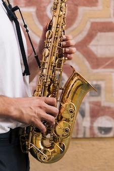 Sluit omhoog de mens die de saxofoon speelt