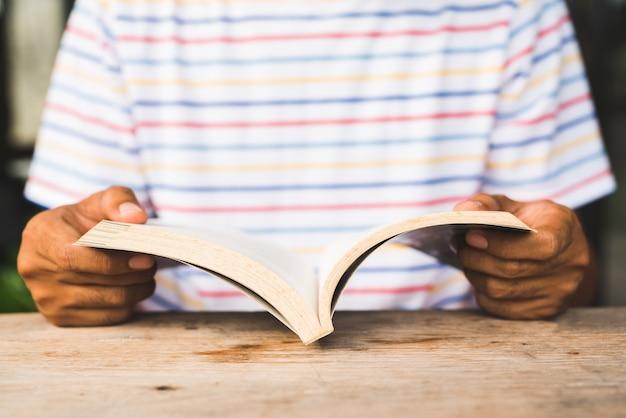 Sluit omhoog de mens die een boek lezen.