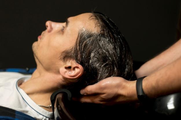 Sluit omhoog de mens die zijn haar krijgt gewassen
