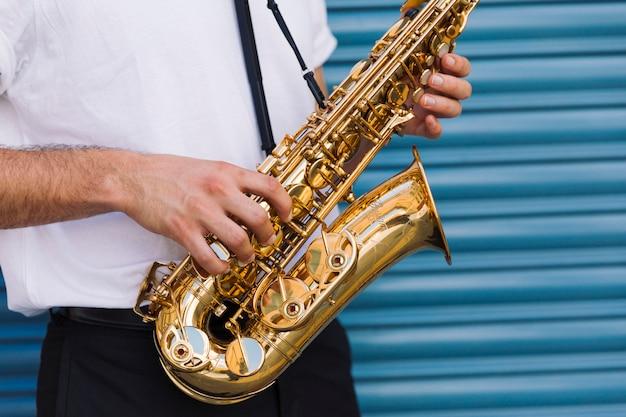 Sluit omhoog de saxofoon van de musicusholding