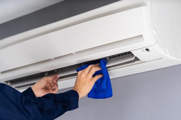 Sluit omhoog de schoonmakende airconditioner van de technicusdienst met doek