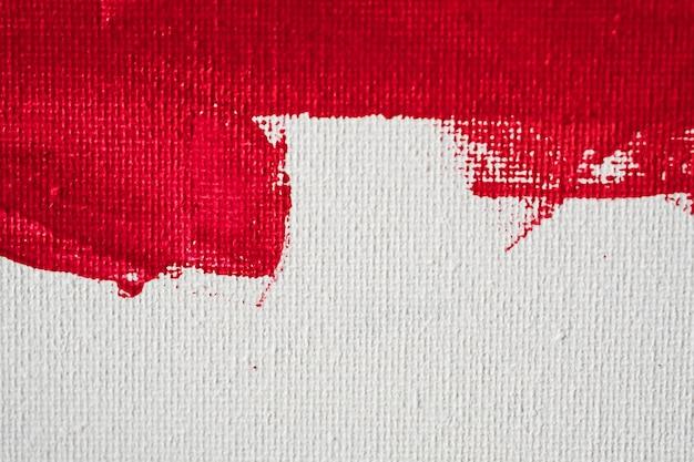 Sluit omhoog de verf van de textuur rode kleur op witte canvasachtergrond