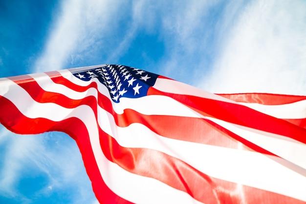 Sluit omhoog de vlag van de verenigde staten van amerika op de blauwe hemelachtergrond. amerikaanse onafhankelijkheidsdag, 4