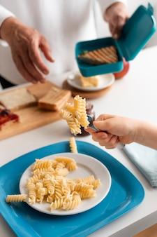 Sluit omhoog de vork van de kleinkindholding met deegwaren