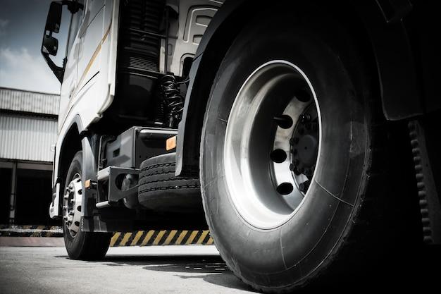 Sluit omhoog de vrachtwagenwielen van semi vrachtwagenparkeren bij pakhuis
