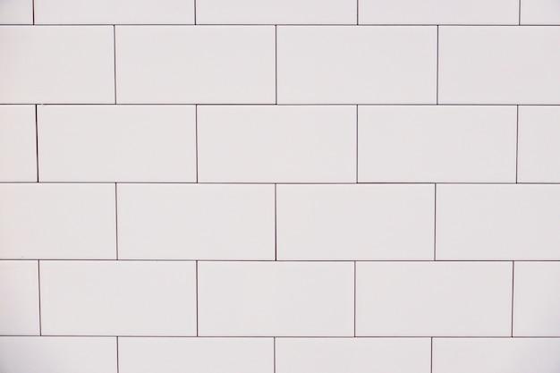 Sluit omhoog de witte uitstekende muur van de keramische baksteentegel