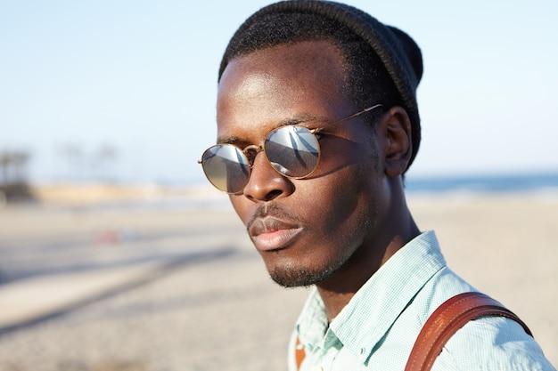 Sluit omhoog de zomer openluchtportret van knappe modieuze amerikaanse student afro in gespiegelde lenszonnebril die gang op strand na universiteit hebben