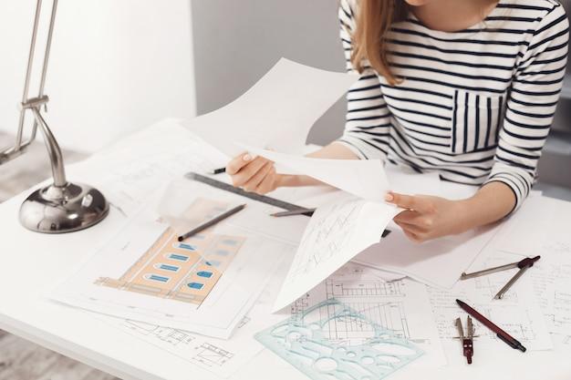 Sluit omhoog detail die van vrouwelijke ingenieur gestreepte kleren dragen zittend bij witte grote lijst, kijkend door documenten, werkend aan bouwproject.