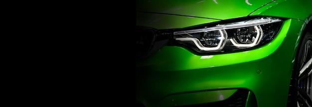 Sluit omhoog detail groene moderne autokoplampen met geleide technologie op zwarte vrije ruimte als achtergrond aan linkerkant voor tekst.
