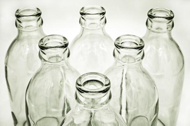 Sluit omhoog detail van glasflessen op witte achtergrond.