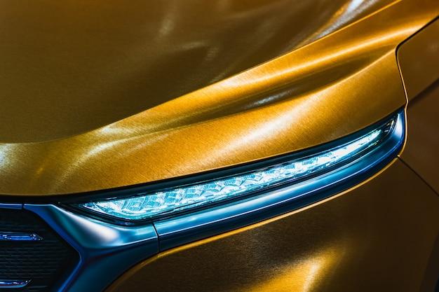 Sluit omhoog detail van koplamp van moderne luxesportwagen die wordt geschoten.