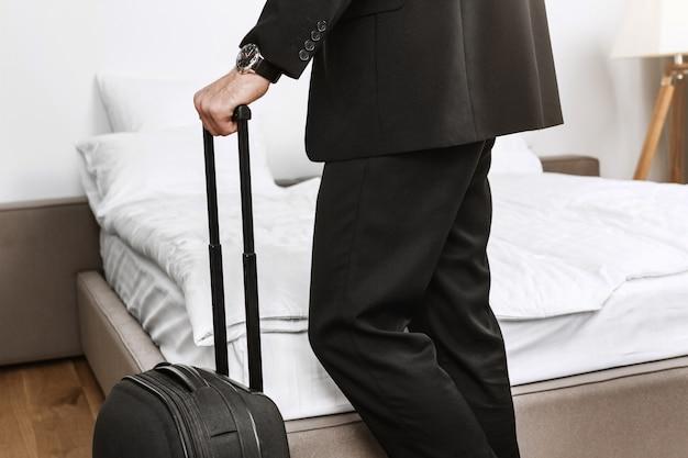Sluit omhoog detail van modieuze zakenman in de zwarte koffer van de kostuumholding in handen die hotelruimte gaan verlaten en door vliegtuig van zakenreis naar huis vliegen.