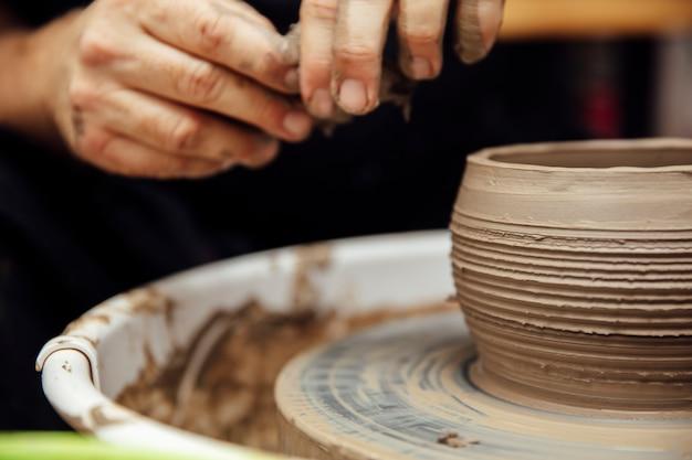 Sluit omhoog detailmening bij een kunstenaar maakt kleiaardewerk op een rotatiewiel