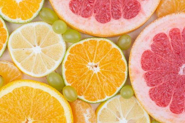 Sluit omhoog diverse plakjes citrusvruchten en druiven.