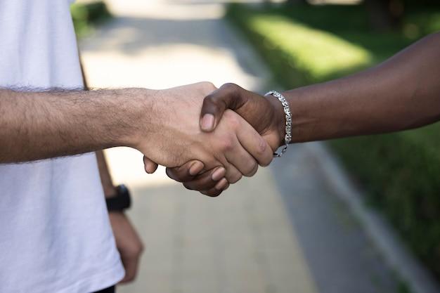 Sluit omhoog diverse vrienden die handen schudden
