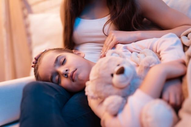 Sluit omhoog dochter slaapt laat op nacht op moederschoot.