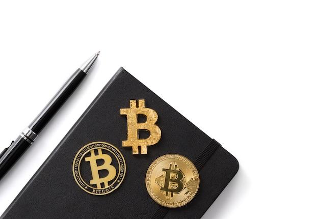 Sluit omhoog drie bitcoinmuntstukken, blocnote en pen die op wit wordt geïsoleerd.
