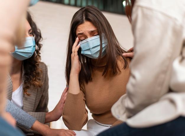 Sluit omhoog droevige vrouw die masker draagt