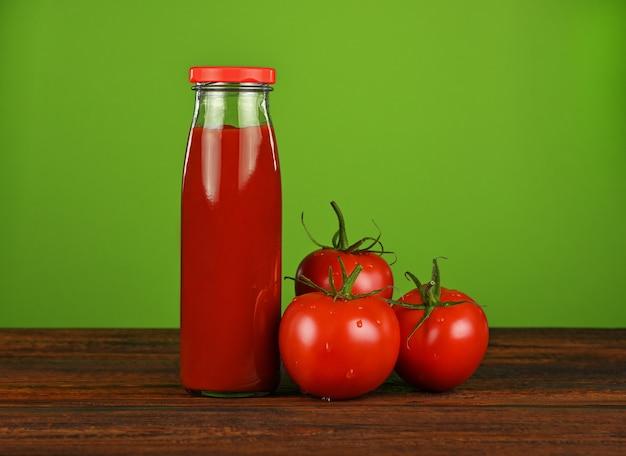 Sluit omhoog één glasfles ketchupsaus en verse rode tomaten op houten lijst over groene muur met exemplaarruimte, lage hoekmening