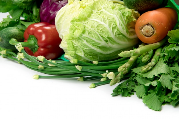 Sluit omhoog een groene kruidenierswinkelzak van gemengde organische groene groenten op wit