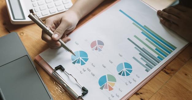 Sluit omhoog een mens die over financieel met calculator op zijn kantoor werken om uitgaven, boekhoudingsconcept te berekenen