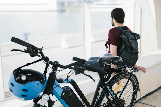 Sluit omhoog elektrische fiets met de zittingsmens op achtergrond